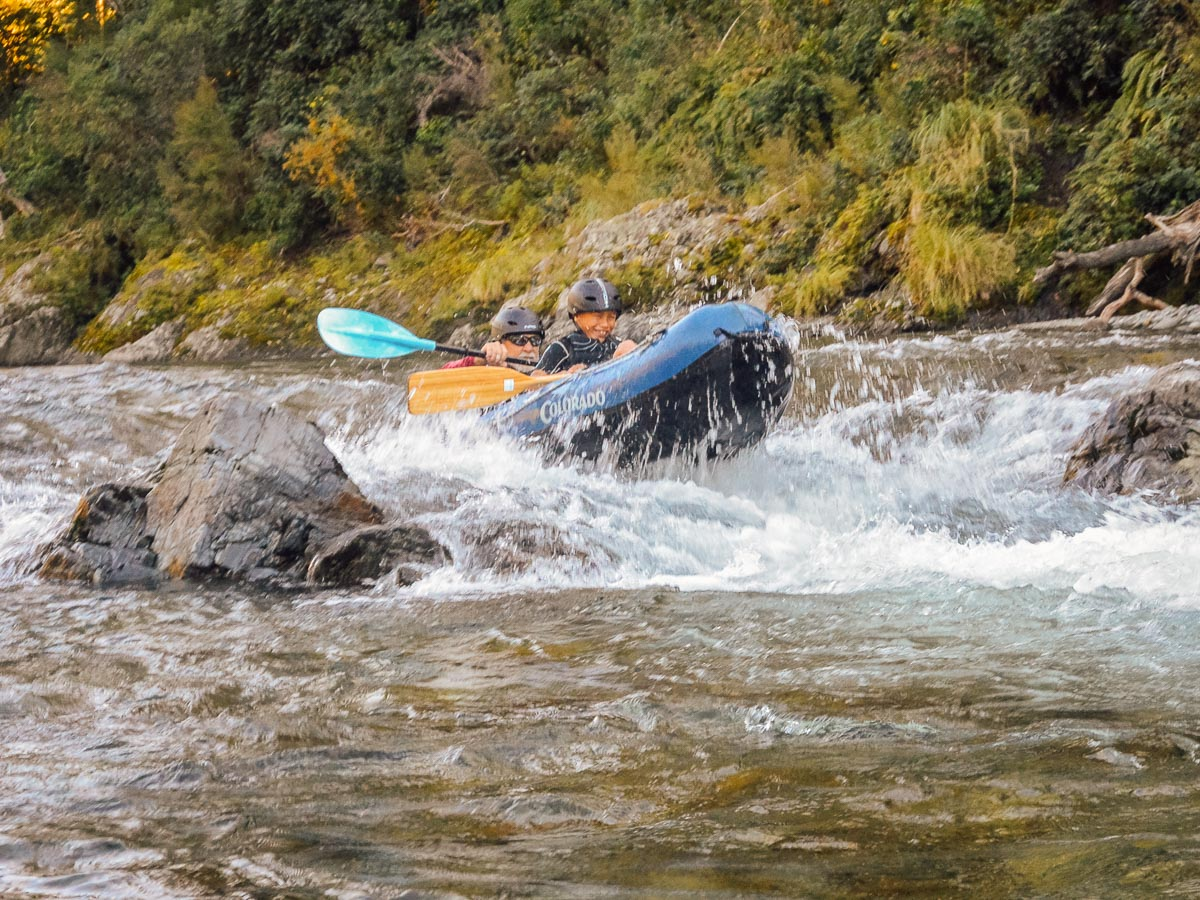 Dad and son kayaking rapids at the Pelorus river