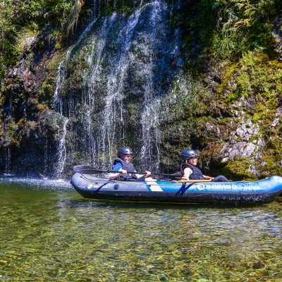 Kids kayaking close to the falls at the Pelorus river