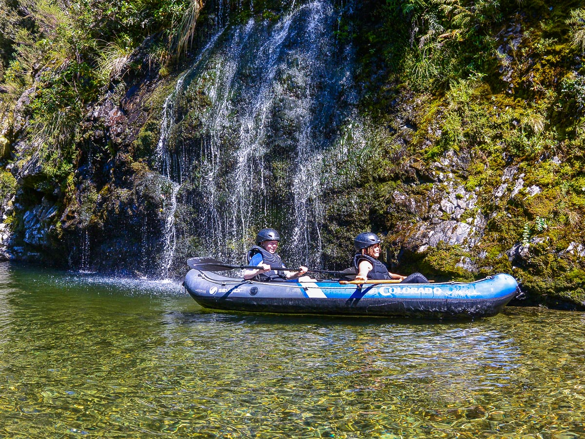 Kids kayaking close to the falls at the Pelorus river