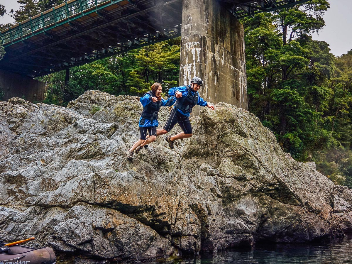 Couple jumping into the Pelorus river, NZ
