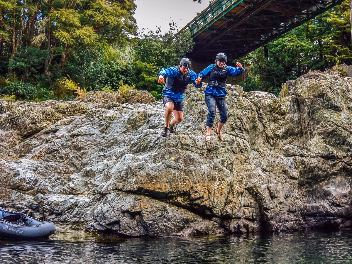 Couple jumping into the Pelorus river