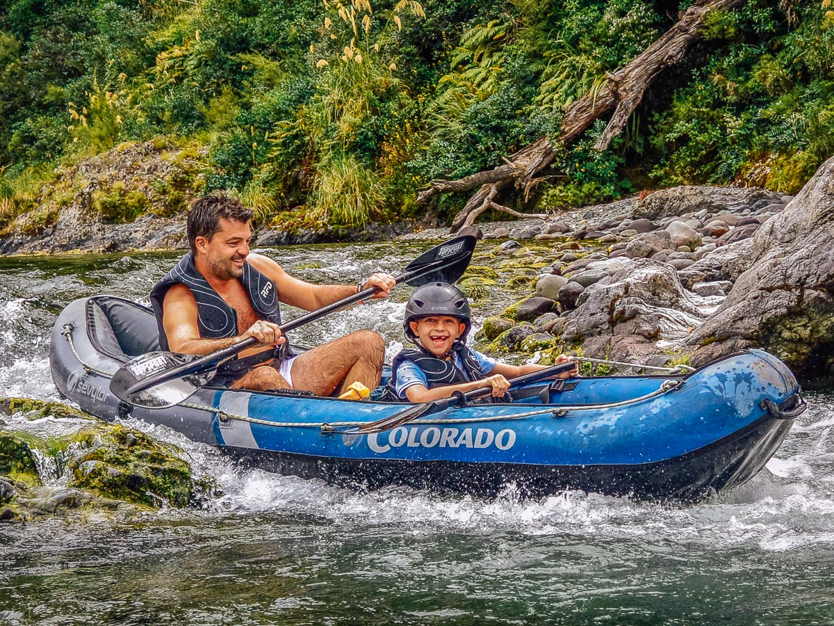 Dad and son kayaking rapids
