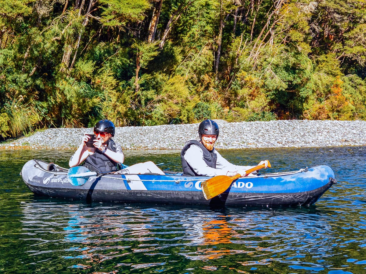 Couple taking pictures while kayaking on the Pelorus river