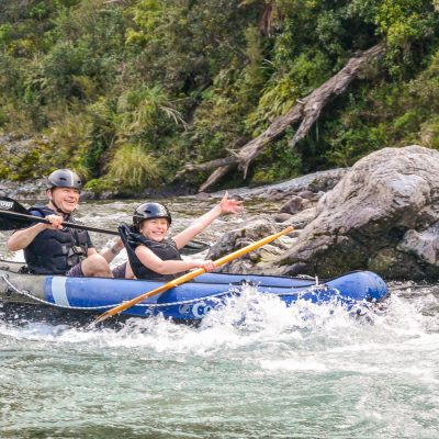 Happy couple kayaking rapids in NZ