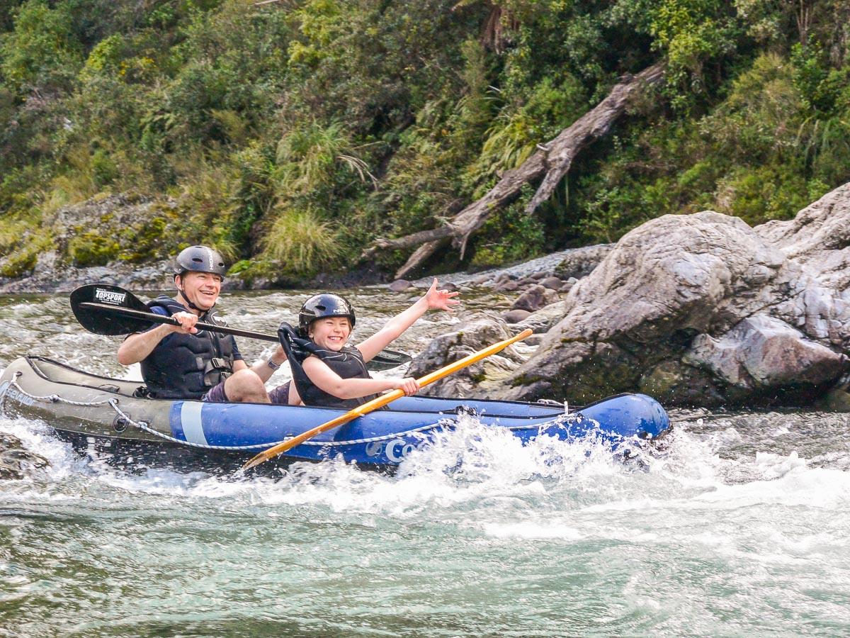 Happy couple kayaking rapids in NZ